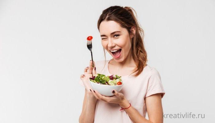 красивая девушка кушает салат, держит вилку в руках