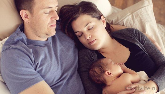 молодая пара спит с грудным ребенком