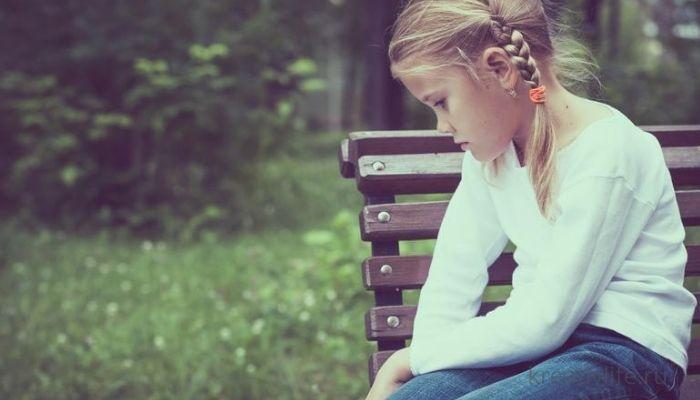 девочка грустная сидит на лавочке
