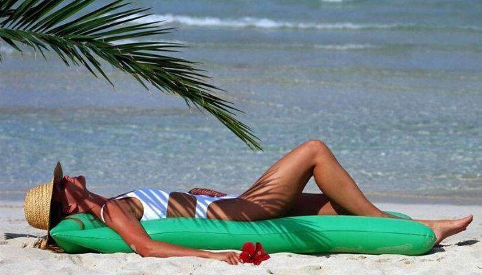 Женщина загорает на солнце на пляже. Солнечный ожог